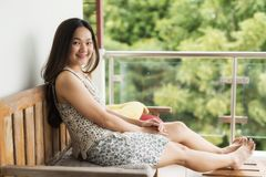 Cute girl relax at blacony. Asian beautiful Chinese woman sit on relax chair and table at balcony with natural greenery background. Cute happy girl rest at porch stock photography