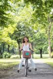 Funny girl legs up riding bike in park. Asian Beautiful funny woman legs up riding bicycle at park with sunlight and foliage bokeh background in summer. People stock photos