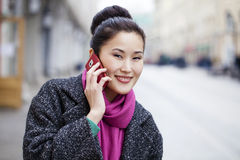 Asian beautiful girl calling by phone. In spring street Royalty Free Stock Image