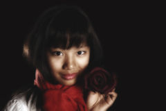 Asian beautiful girl with a smile holds a burgundy rose Stock Photos