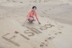 Asian beautiful girl writing word on the beach Royalty Free Stock Photo