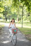 Brunette Asian girl ride bike in park. Asian Beautiful happy woman riding a bicycle at park with foliage bokeh background in summer. People Healthy and sport royalty free stock photography