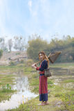 Asian beautiful lady in tribe dress stand near swamp with fishing gear in hand. stock image