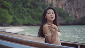 Asian beautiful sensual woman in crochet bikini on the boat. Video of girl sitting on the boat and looking up to the sky in s