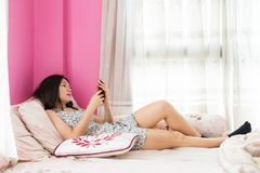 Girl in pajamas play smartphone on bed. Asian beautiful woman on bed play social media, chat, shop online by smartphone. portrait of cute happy Chinese girl in stock photo