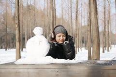 Asian beautiful woman building snowman in garden Stock Photo