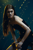 Asian beautiful woman in dress in golden lights in dark Royalty Free Stock Images