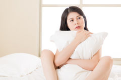 Asian beautiful woman feel unwell sickness sit on bed. Bedroom background Stock Photos