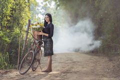 Asian beautiful woman in local dress with old bicycle and flower basket. On the green summer field stock images