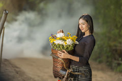 Asian beautiful woman in local dress with old bicycle and flower basket. On the green summer field royalty free stock photography