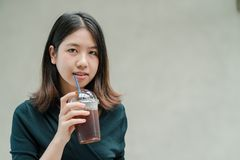 Asian beautiful woman Put on a black shirt, stand to drink cold coffee in the hand with pleasure.  royalty free stock photo
