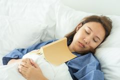 Asian Beautiful Woman Read books while sleeping. Man book cover Drowsiness causes sleep.The concept of adequate sleep. Good sleep royalty free stock photography
