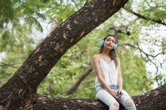 Asian Beautiful woman sit on big tree and listen to online streaming music from smartphone by earbuds. Brunette girl relax in. Summer park royalty free stock photography