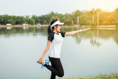 Asian beautiful woman stretching and warming up before running or working out at outdoor royalty free stock photo
