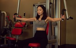 An Asian beautiful woman is training in the gym royalty free stock photography