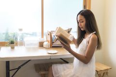 Girl read book and drink coffee near window. Asian beautiful woman with white dress sit near window to read book and drink coffee. People leisure hobby and Royalty Free Stock Photos