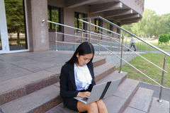 Asian beautiful young female holds in hands laptop and smiling,l Royalty Free Stock Photography
