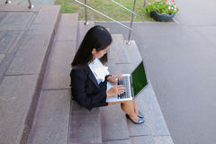 Asian beautiful young female holds in hands laptop and smiling,l Royalty Free Stock Images