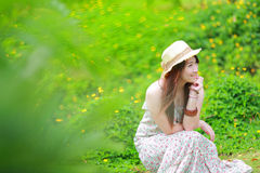 Asian beautiful young girl,wear floral maxi dress. And hat, sitting on the ground at spring Stock Photos