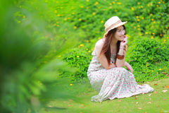 Asian beautiful young girl,wear florals maxi dress. And hat, sitting on the ground at spring Stock Image