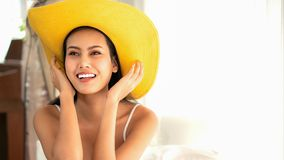 Asian beautiful young happy woman in casual dress with yellow hat in white room with smile