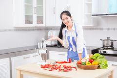 Asian beautiful young woman in cook is mixing batter, looking at stock image