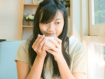 Asian beautiful young woman drinking coffee near window royalty free stock image
