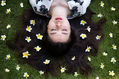 Asian beautiful young woman lying on lawn with flowers royalty free stock photography