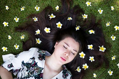Asian beautiful young woman lying on lawn with flowers stock images
