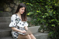 Asian beautiful young woman playing laptop in outdoor garden Stock Photo
