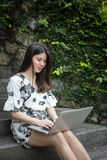 Asian beautiful young woman playing laptop in outdoor garden. On a sunny day Stock Photo