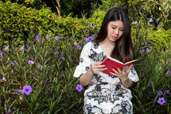 Asian beautiful young woman reading a book in outdoor garden royalty free stock photography