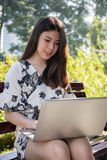 Asian beautiful young woman sitting on the bench with laptop stock photo