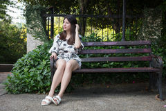 Asian beautiful young woman sitting on bench in outdoor garden Stock Image