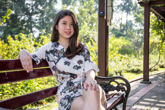 Asian beautiful young woman sitting on bench in outdoor garden royalty free stock photos