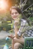 Asian beautiful younger woman toothy smiling face and relaxing in garden Royalty Free Stock Photography