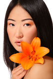 Asian beauty. Beautiful young asian girl with clear makeup and bright flower Royalty Free Stock Photos