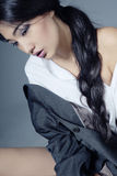 Asian beauty. Sad Asian lady with long hairs sitting in the studio Stock Images