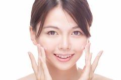 Asian beauty applying cream to face Royalty Free Stock Photo