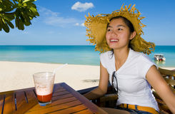 Asian beauty at the beach. Beautiful asian woman with cocktail at the beach royalty free stock image