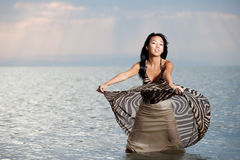 Asian beauty in dress. Asian beauty girl stay on the beach in water, play with dress Stock Images