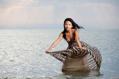 Asian beauty in dress. Asian beauty girl stay on the beach in water, play with dress Royalty Free Stock Images