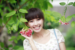 Asian beauty with flowers. Happy Asian beauty with flowers outdoor Royalty Free Stock Photography