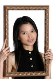 Asian Beauty in a frame. Attractive young Asian woman framing her face with a vintage frame Royalty Free Stock Images