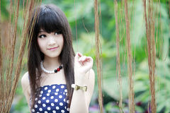 Asian beauty in the garden. Charming Asian beauty smiling in the garden Stock Photography