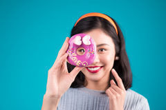 Asian beauty girl holding pink donut against her eye. Retro joyf Royalty Free Stock Photo
