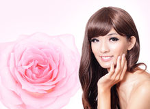 Asian beauty hand touch face with pink rose Royalty Free Stock Images