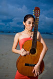 Asian beauty holding a guitar at the beach. Fashion asian model holding a guitar up high at the beach Royalty Free Stock Image