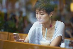 An asian beauty looking at smartphone in coffee shop Stock Photo