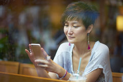 An asian beauty looking at smartphone in coffee shop Stock Photography